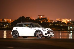 White Mini cooper parked near river, high rise in the background at sunset